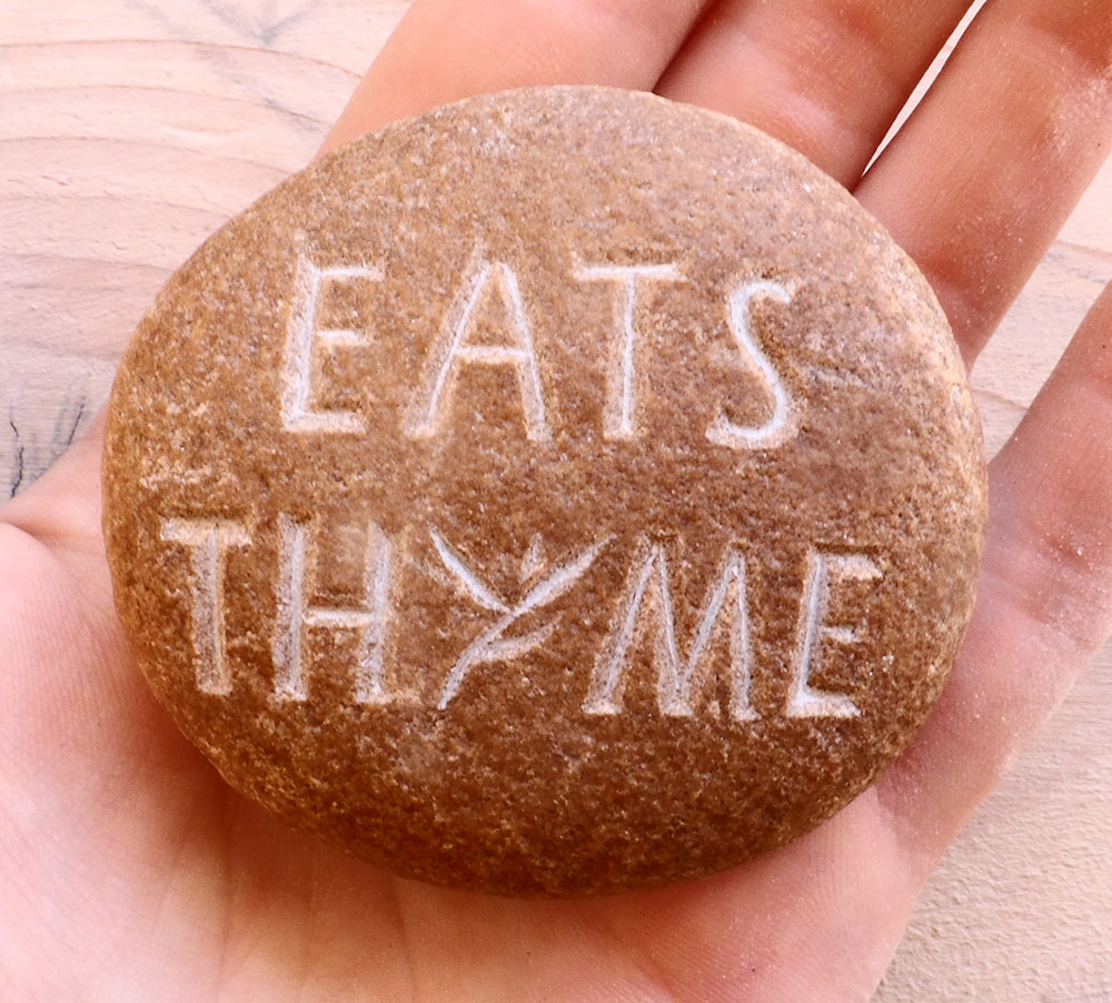 Logo de l'épicerie et restaurant libanais Eats Thyme gravé dans un galet