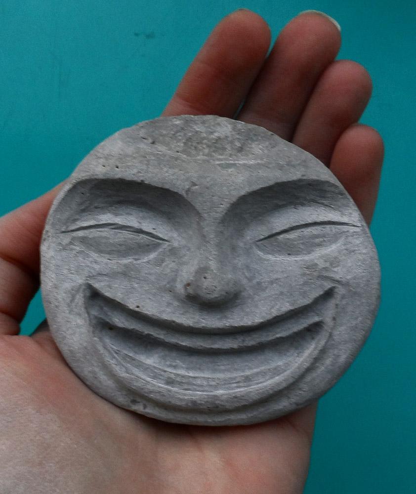 Galet dans lequel est sculpté un visage heureux qui rit