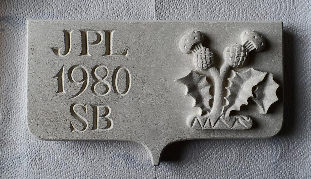 Plaque funéraire en savonnière : chardon lorrain en bas-relief et lettres romaines gravées