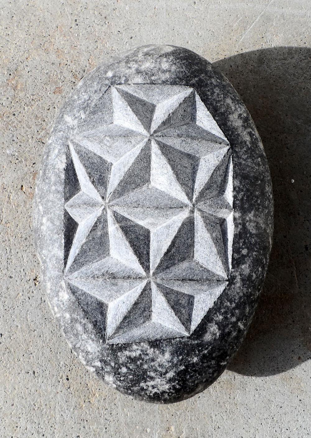Galet avec motif géométrique fait de triangles gravés