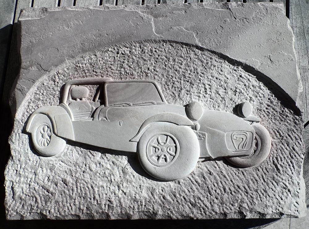Bas-relief représentant une Lotus Seven en grès des Vosges bigarré